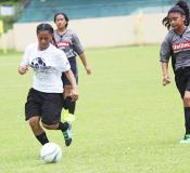 An Ilaoa & To'omata player dribbles away from a Taputimu Youth defender
