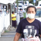 A woman walking on the street in Apia wearing a mask