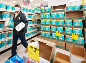 A masked customer grabs two packages of toilet paper at Longs Drugs in Moiliili.