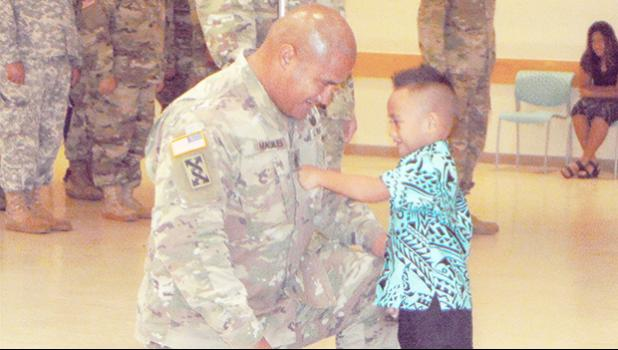 Newly pinned 1ST Sgt. Nathan Magalei of the 411th Engineer Battalion of the local U.S. Army Reserve and his son, Eisa Magalei, who had the honor of pinning his father