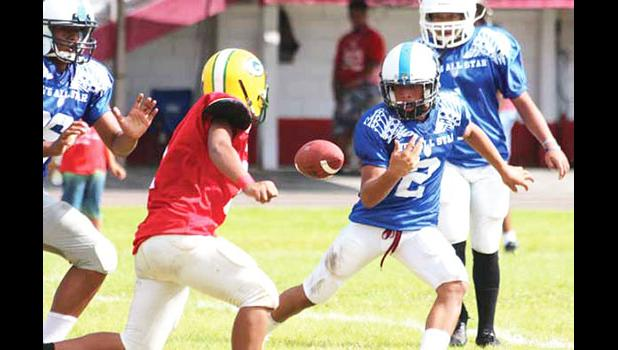 Steven Sinoti of the Blue All-Star team loses the football before he is tackled by a Red team defender during the opening half of the All-Star game last Saturday morning. The Red team won 14-8. [photo: TG]