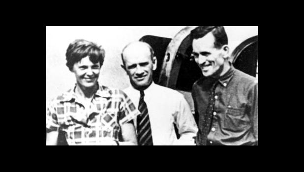 In this file photo taken on or about July 2, 1937, American aviator Amelia Earhart, left, and her navigator, Fred Noonan, right, pose beside their plane with gold miner F.C. Jacobs at Lae, New Guinea just before Earhart and Noonan took off in a flight to Howland Island on July 2, during which they disappeared somewhere in the Pacific. (AP Photo, File)