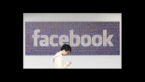 In this June 11, 2014, file photo, a man walks past a Facebook sign in an office on the Facebook campus in Menlo Park, Calif. Facebook announced Thursday, April 6, 2017, it is launching a tool to help users spot false news articles on the site. The tool, similar to others around privacy and security, will be available to users in 14 countries, including the U.S. Users will see it for a few days when they open Facebook. (AP Photo/Jeff Chiu, File)