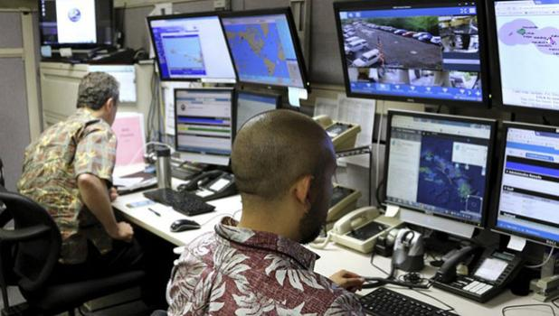 In this Dec. 1, 2017 file photo, Hawaii Emergency Management Agency officials work at the department's command center in Honolulu. A Hawaii employee who mistakenly sent an alert warning of an incoming ballistic missile earlier this month, creating a panic across the state, thought an actual attack was imminent, the Federal Communications Commission said Tuesday, Jan. 30, 2018. (AP Photo/Caleb Jones, File)
