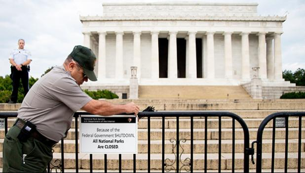 "In this Oct. 1, 2013, file photo, A U.S. Park Police officer watches at left as a National Park Service employee posts a sign on a barricade closing access to the Lincoln Memorial in Washington. The world won't end if a dysfunctional Washington can't find a way to pass a funding bill before this weekend. That's the truth about a government ""shutdown."" The government doesn't shut down. It's a crummy way to run a government, sure, but Social Security checks will still go out. Troops will remain at their post"