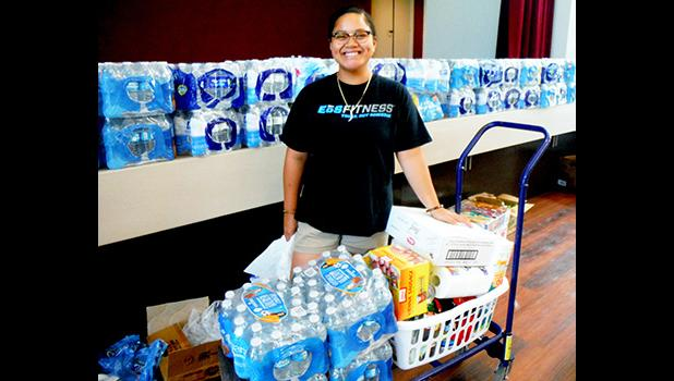 ASCC student Feliciamere P. Elisara, whose Vailoa home was destroyed by Cyclone Gita, receives food, water and clothing during the College's assistance drive last week for students affected by the cyclone. The ASCC Marketing Committee organized effort, with assistance from the Student Government Association and the College's student clubs.  [Photo: J. Kneubuhl]