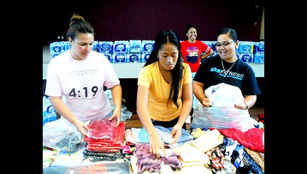 ASCC Student Government Association president Christina Toilolo (center) sorts through donated clothing, with assistance from Jennifer Si'ilata (left) of Operation Love, during the College's assistance drive last week for students affected by Cyclone Gita.  [Photo: J. Kneubuhl]