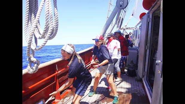 "During an oceanographic research sail aboard the vessel ""Robert C. Seamans,"" Sea Education Association staff lead ASCC students in the appropriate line hauling method to raise the main sail, the largest sail on the ship. (Photo. S. Woofter)"