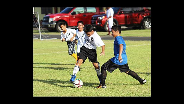 An SPA player, left and a St. Theresa opponent of the Boys 3-5 bracket in action during Match Day 2 of the 2016 FFAS Private Elementary Schools soccer league at the Kanana Fou Seminary Field on Thursday, Oct. 20, 2016.  [FFAS MEDIA/Brian Vitolio]