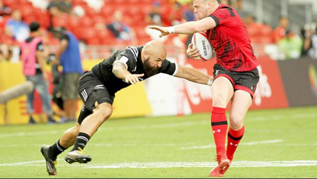 NZ Joe Ravouvou plays with a Wales defender as he scores a try in the All Blacks 36-14 victory over Wales at the Singapore Sevens, Day 1, National Stadium, Singapore. [Photo: Barry Markowitz]