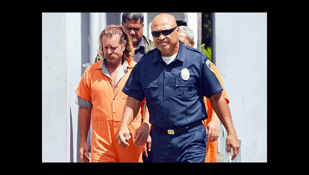 In this Oct. 5 Samoa News file photo, Dean J. Fletcher (left) is escorted by a police officer after his initial appearance in District Court the previous day.  [photo: AF]