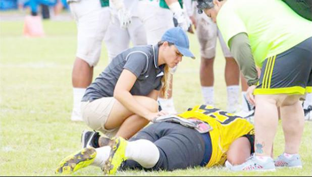 American Samoa's only Certified Athletic Trainer Florence Wasko attended the IOC World Conference last week for an update on the latest within the field of sports medicine. She works for ASDOE — Athletic Division — and is seen here during a local football game treating a player who was injured during play.  [SN file photo]