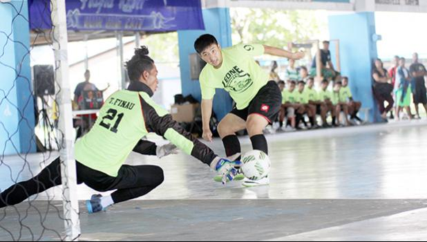 Gun Kang (#9) of Ilaoa & To'omata watches his shot being deflected by Vaiala Tongan goalkeeper Kinikinilau Pouli during their 2017 Futsal Tournament's pool game at Samoana High School's gymnasium on Saturday, May 6, 2017.  [FFAS MEDIA/Brian Vitolio]