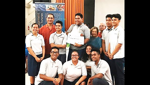 Pictured are the students from Manumalo — with their $600 check — along with one of American Samoa's three members on the Council, Taotasi Archie Soliai, and Dept. of Marine and Wildlife Resources director Va'amua Henry Sesepasara. [photo: BC]