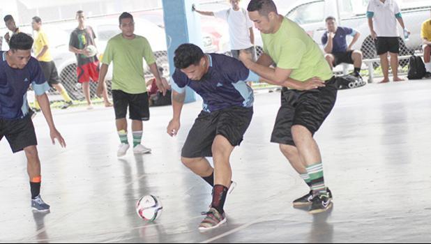 Tafuna Jets 1's Harry Matau holds off Lion Heart B's Charmaney Faatupuinati on Match Day 3 of the 2017 FFAS Futsal Tournament at Samoana High School's gym in Utulei on Saturday, May 20, 2017.  [FFAS MEDIA/Brian Vitolio]