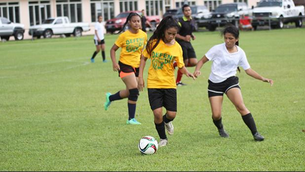 Ama Faleao of Leone tries to dribble away from Maricar Parungo of the Fa'asao Cougars during an ASHSAA varsity girls' soccer game on Saturday, Feb. 24, 2018 at Pago Park Soccer Stadium.  [FFAS MEDIA/Brian Vitolio]