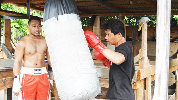 Petelo Matagi helping one of the young fighter during their training last week at the American Samoa Boxing Federation training spot in Tafuna. [photo AF]