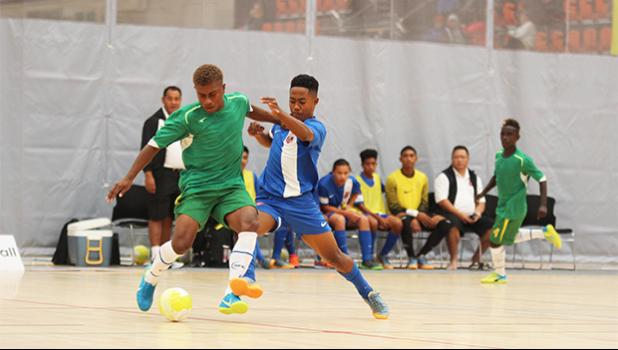 American Samoa's Henry Milo Tiatia gets physical on the ball with a Solomon Islands' opponent during a game of the OFC Youth Futsal Tournament at Bruce Pulman Arena in Auckland, New Zealand on Wednesday, October 4, 2017.  [FFAS MEDIA/Brian Vitolio]