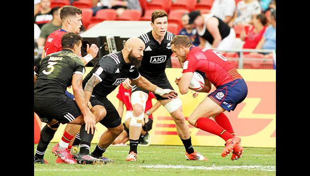 NZ All Blacks 7s Captain, DJ Forbes, demonstrates perfect form in setting up to tackle a Scotland player in NZ's 22-21 victory over Scotland at the Singapore Sevens, Day 1, National Stadium, Singapore.  [Photo: Barry Markowitz]
