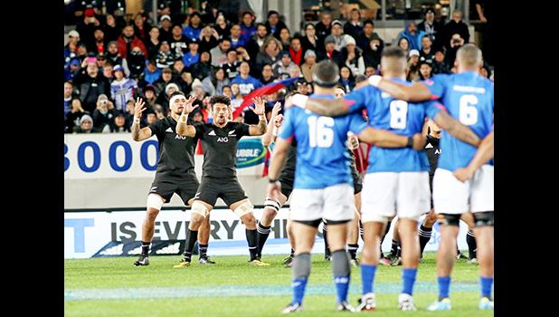With Samoa flags to their back, the NZ All Blacks respond to Samoa's Siva Tau with their legendary Haka.  The New Zealand All Blacks defeated Manu Samoa 15s 78-0 at Eden Park, Auckland, New Zealand.   [Photo: Barry Markowitz]