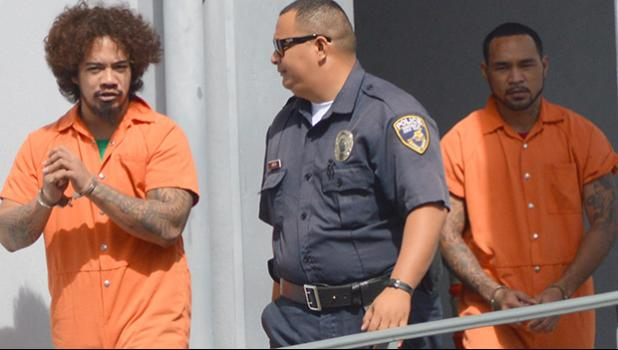 DPS police officer escorting prison escapees Joseph Iosefa Iakopo and Ryan Pite outside the District Court after their initial appearance yesterday morning.  [photo: AF]