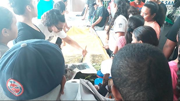 Local artist Reggie Meredith-Fitiao showing kids from the FIT summer program, how to 'elei using 'ulu leaves, fala, and potato stamps. [Courtesy photo]