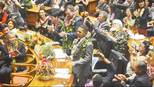 Hawai'i state Rep. Cedric Solosolo Asuega Gates (standing-front) being recognized along with another lawmaker, on the floor of the Hawai'i state House of Representatives on Jan. 18 — the opening of the Hawai'i Legislature. Family members of lawmakers were also on the floor behind them.  [photo: Rep. Gates Office]