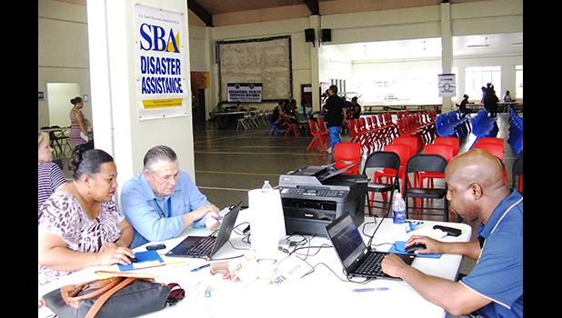 A US Small Business Administration representative (right) providing assistance to two local residents, affected by Tropical Storm Gita, at the Disaster Recovery Center at the Pago Pago Community Youth Center yesterday.  [photo: SBA]