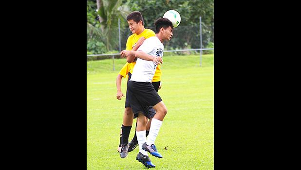 A Samoana Sharks player heads the ball forward while being contested in the air by a Tafuna Warriors' opponent during an ASHSAA Boys' JV soccer game on Tuesday, March 27, 2018 at Pago Park Soccer Stadium.  [FFAS MEDIA/Brian Vitolio]