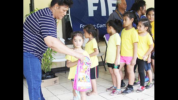 A young participant of the 2017 FFAS Summer Youth League receives her bag filled with school supplies from FFAS executive committee member Saili Ott on July 15 at Pago Park Soccer Stadium. [FFAS MEDIA/Brian Vitolio]