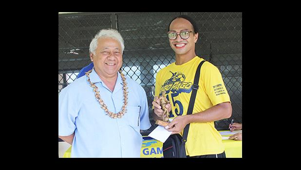 Sam Tualaulelei, a Pago Youth defender, receives his MVP trophy from FFAS President Faiivae Iuli Alex Godinet, left, for the 2016 FFAS National League on Saturday, November 26, 2016.   [FFAS MEDIA/Brian Vitolio]