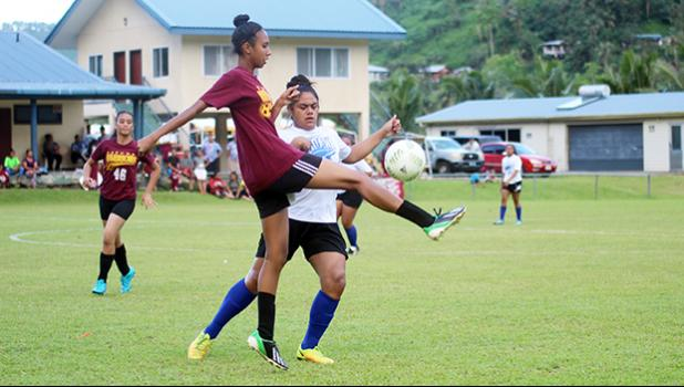 A Tafuna Warriors' player clears the ball away from a Samoana opponent during the championship game of the ASHSAA Girls' J-V division on Wednesday, March 14, 2018 at Pago Park Soccer Stadium.  [FFAS MEDIA/Brian Vitolio]