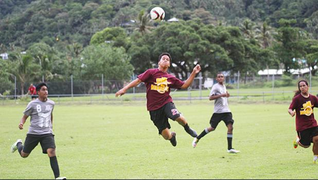A Tafuna Warriors' player heads the ball away from SPA's Peter Reid during their ASHSAA Boys semifinal game this past Tuesday at Pago Park Soccer Stadium.  [FFAS MEDIA/Brian Vitolio]