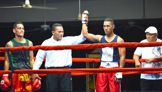 American Samoa raising star, George Tanoa Jr (right) raising his hand after a knockout win over his tough opponent, Tasi Tonelafo (left) of Tumua ma Pule boxing club in the middleweight division during the American Samoa Flag Day 2018 Championship Boxing between the two Samoas last Saturday night at the old Bowling Alley in Tafuna.  [photo by AF]