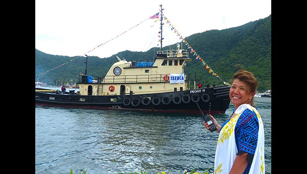 Port Administration director, Taimalelagi Dr. Claire Poumele, posed for a Samoa News photo on the main dock yesterday with Port's second tugboat, Peggy H, in the waters of Pago Pago Harbor.  The tugboat, will be renamed Iseula and is the second one for the Port Administration as required by US Coast Guard regulations.  [photo: Leua Aiono Frost]