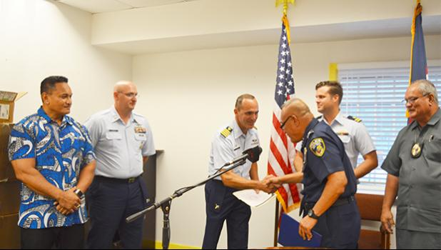 Falana'ipupu Taase Sagapolutele shaking hands with U.S Coast Guard Sector Commander from Honolulu, Capt. Michael C. Long after the DPS Deputy Commissioner received his Certificate of Recognition last week. See story for details.  [photo: AF]