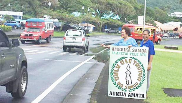 Amata waving behind a thank you sign.  A passerby stops to help out.