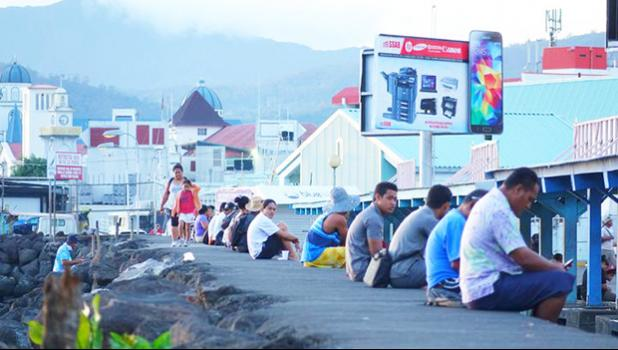 Samoa residents sit along the seawall in downtown Apia