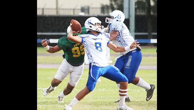 Anthony Feala of the Sharks, flexing to pass to Elliot Lelei for another touchdown conversion in the second quarter of their varsity game against the Lions last Saturday afternoon. Feala led the Sharks in a dominating 34-8 victory.  [photo: TG]