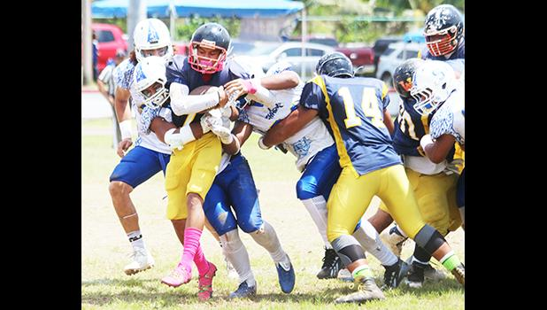 The playmaker for the Wildcats, Iosefa Mauga is stopped immediately by a host of Samoana Sharks behind the line of scrimmage for a loss during the third quarter of their varsity match up last Saturday morning. Samoana's defensive unit shut out the Wildcats completely in a 49-0 victory, the first team to ever shut out Nu'uuli this regular season.  [photo: TG]
