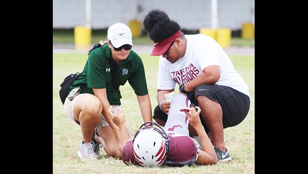 An injured Tafuna Warrior being tended to by ATC Florence Wasko and Warriors assistant coach Travis Pavihi during the opening quarter of the Warriors vs. Sharks JV match up last Saturday morning.  [photo: TG]