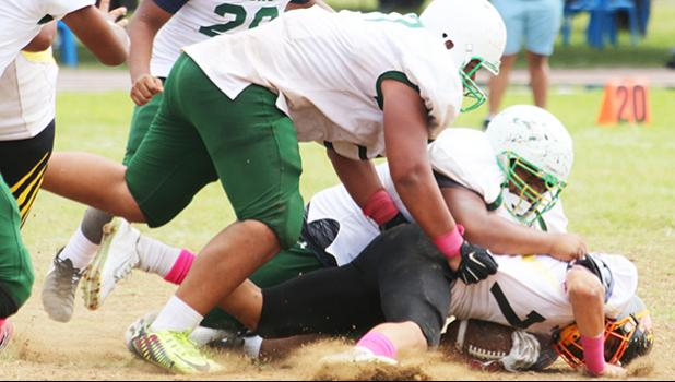 Nu'uuli Wildcats quarterback is immediately sacked hard in the backfield by Cyan Fiatoa during the final quarter of their scoreless JV game that was held this past Saturday morning at the Veterans Memorial Stadium.  [photo: TG]