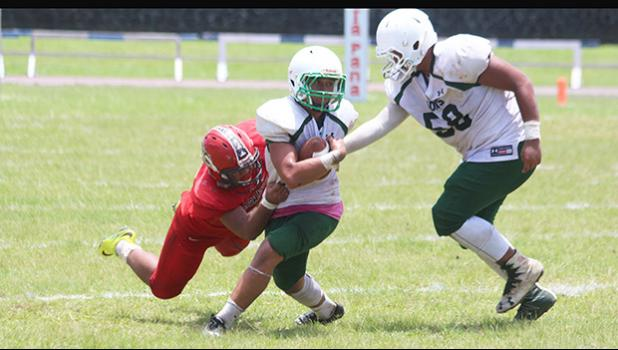 Ron Fuala'au of the Lions immediately stopped in the backfield by Jake Umu of the Vikings during the second half of their junior varsity match up last Saturday morning. Fuala'au helped the Lions to a 26-14 win, their first victory of the season. [photo: TG]