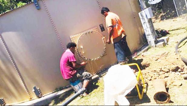 Two ASPA employees working on water tank in Aunu'u.
