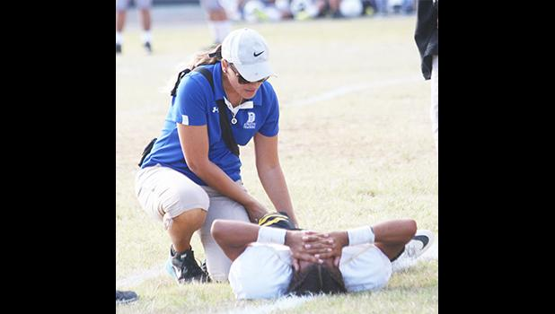 ASHSAA ATC Florence Wasko tends to an injured Nu'uuli Wildcat on the field during a Junior Varsity game against the Tafuna Warriors last Friday evening.  [photo: TG]