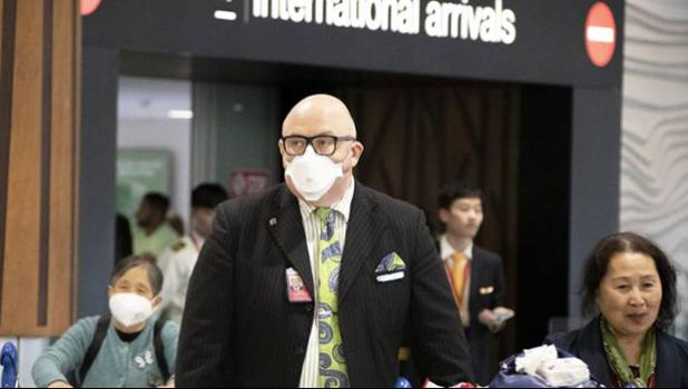 Travellers wearing face masks exit the arrivals hall at Auckland International Airport