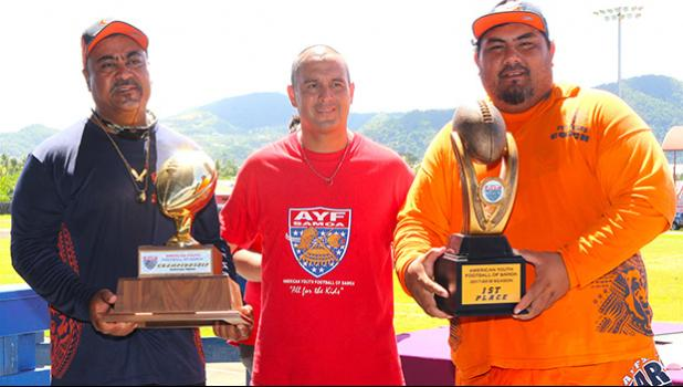 AYFS Bears Head Coach Sa Suluai with his Offensive Coordinator Keith Leuta receiving the AYFS Perpetual Trophy for the third time, along with the 1st Place trophy for being 'Back-2-Back' Undefeated Champs during the awards ceremony last Saturday. Also pictured is AYFS President Victor Avalos. [photo: TG]