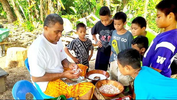 Youngsters watch as palusami is prepared for the umu