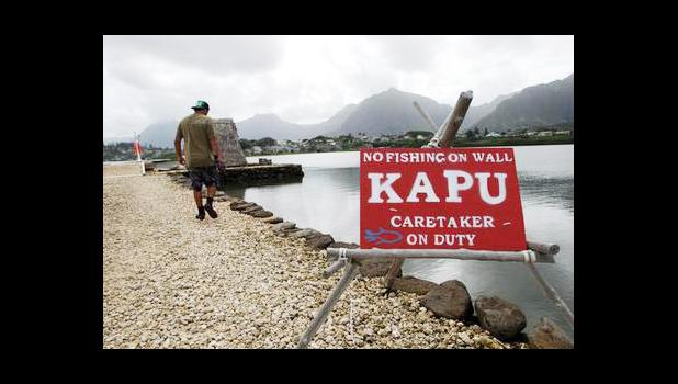 In this Friday, Dec. 2, 2016 photo, Conservation International's Luka Mossman, who restores and researches Native Hawaiian fishponds, walks along a barrier wall on Heeia fishpond in Kaneohe, Hawaii. As traditional commercial fishing is threatening fish populations worldwide, U.S. officials are working on a plan to expand fish farming into federal waters around the Pacific Ocean. Some see the move toward aquaculture as a promising solution to overfishing and feeding a hungry planet. But critics say the indus