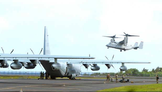 A C-130 on the tarmac and an MV-22 Osprey military plane overhead at Pago Pago International Airport